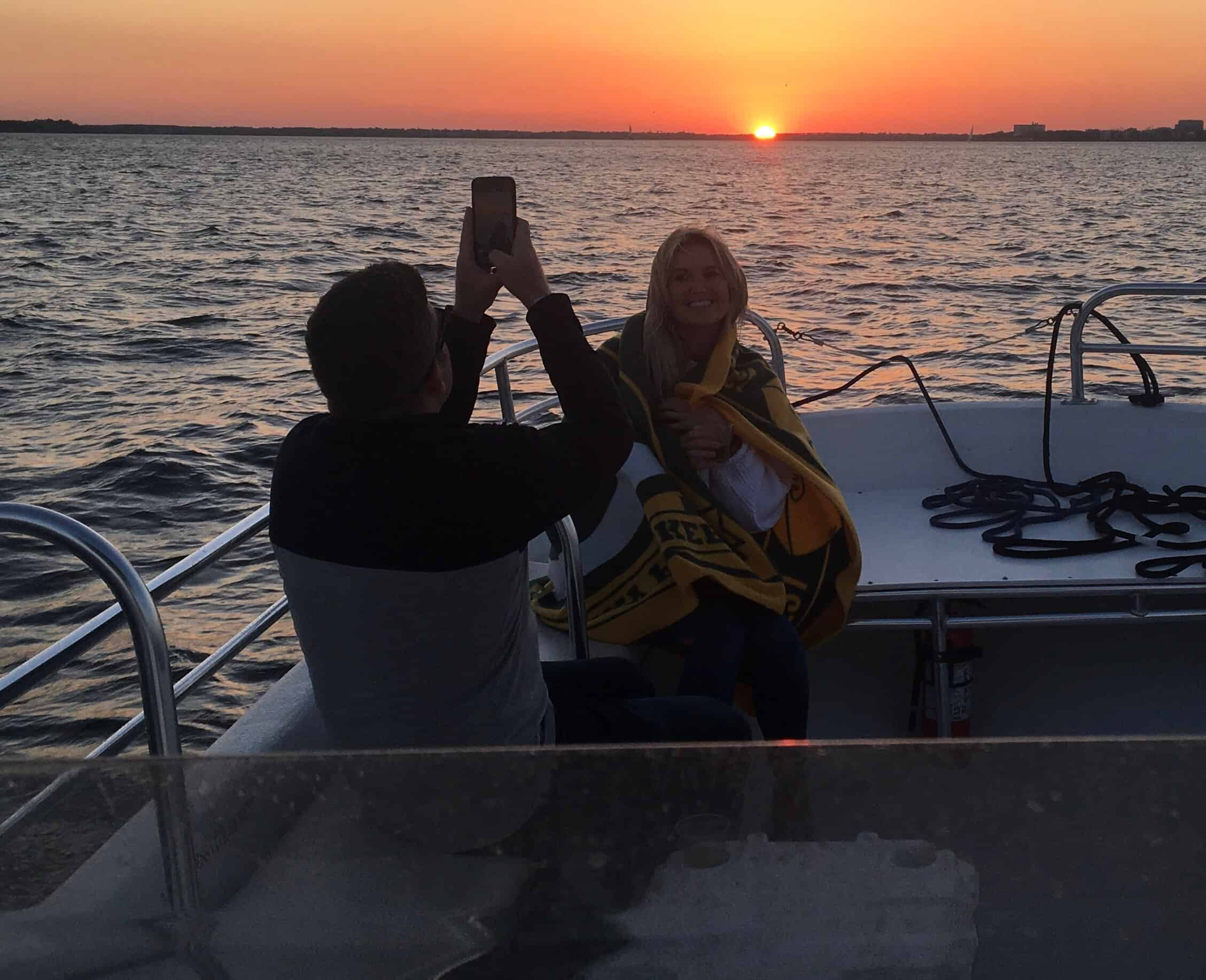 Woman getting her picture taken on the boat with the sunset behind her. Sunset booze cruise Charleston, SC